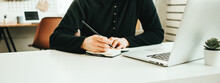 Woman Working With Notepad And Pencil Near Laptop And Mobile Phone On The Table. Hands Clode-up