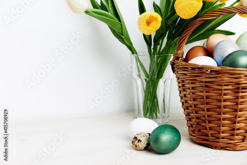 Fototapeta Easter eggs in a basket and yellow tulips in a vase In a bright room obraz