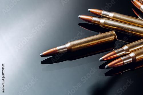 Fotografija Rifle bullets or cartridges on black shiny background