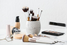 Set Of Makeup Brushes And Decorative Cosmetics On Light Background
