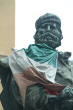 Vertical Shot Of The Famous Giuseppe Garibaldi Bronze Statue With An Italian Flag In Parma, Italy