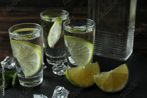 Canvas Print Tray with bottle and shots of vodka, lime and ice on wooden background