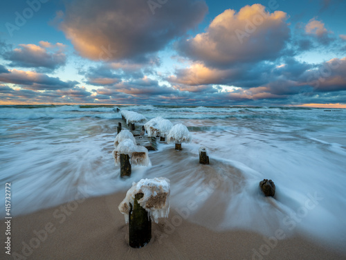 Beautiful winter sea landscape. Ice breakwaters, waves and fiery sunset. Artistic photography.. © Mike Mareen