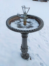 Vertical Shot Of An Ancient Frozen Fountain In A Park Covered By Snow
