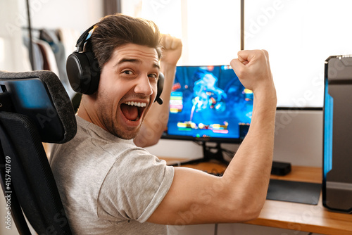 Excited guy making winner gesture while playing video game on computer