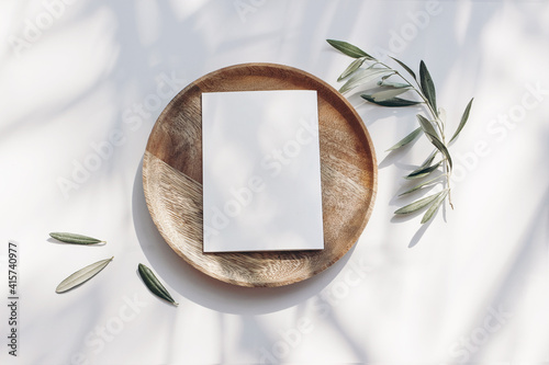 Summer wedding stationery mock-up scene. Blank greeting card, wooden plate, olive tree leaves and branches in sunlight. White table background with palm shadows. Feminine flat lay, top view. © tabitazn
