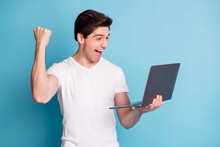 Portrait Of Astonished Man Arm Hold Laptop Fist Up Open Mouth Scream Yeah Isolated On Blue Color Background
