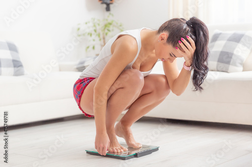 Fototapeta Young woman squats on a scale holding her head frsutrated over gaining weight