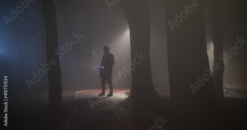 Fotografie, Obraz detective with a flashlight in the forest at night in the fog