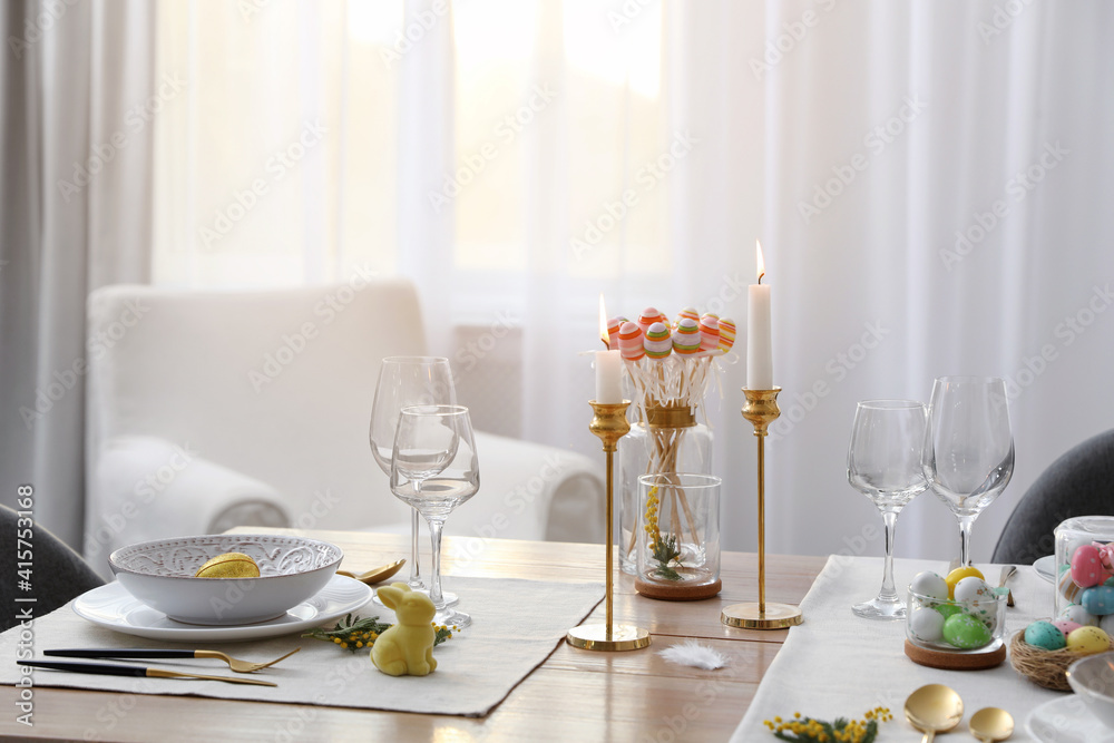 Fototapeta Beautiful Easter table setting with burning candles and floral decor indoors
