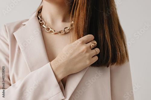 Slika na platnu Woman in light beige jacket wearing golden chain necklace.