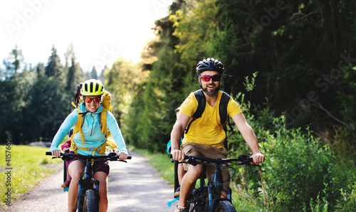 Fototapeta Family with small children cycling outdoors in summer nature. obraz
