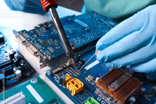 Obraz Technician repairing electronic circuit board with soldering iron at table, closeup - fototapety do salonu