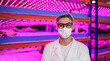 Leinwandbild Motiv Worker with face mask looking at camera on aquaponic farm, sustainable business and coronavirus.