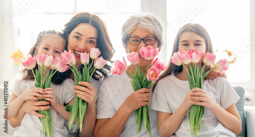 Fototapeta Happy women's day! Child daughters are congratulating mom and granny giving them flowers tulips. Grandma, mum and girls smiling and hugging. Family holiday and togetherness. obraz