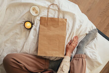 Woman Sitting On The Bed With Candles And Empty Craft Paper Bag.