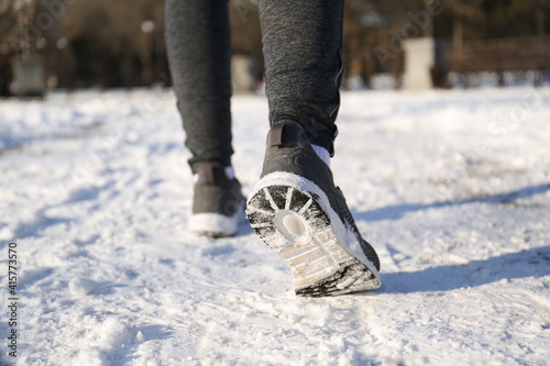 Fototapeta Woman running along park on winter day, closeup. Outdoors sports exercises obraz
