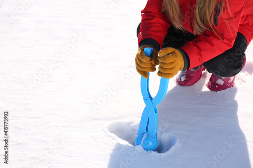 Fototapeta Little girl playing with snowball maker outdoors, closeup obraz