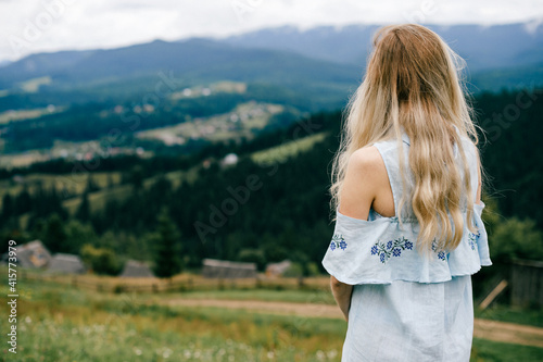 Obraz Young attractive elegant blonde girl in blue romantic dress posing back over picturesque landscape - fototapety do salonu