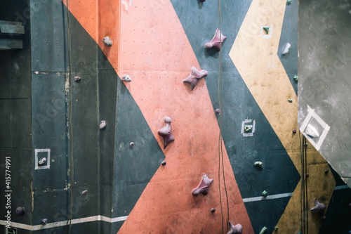 Obraz na plátně Close up photo of a rock climbing wall with climbing holds in gym
