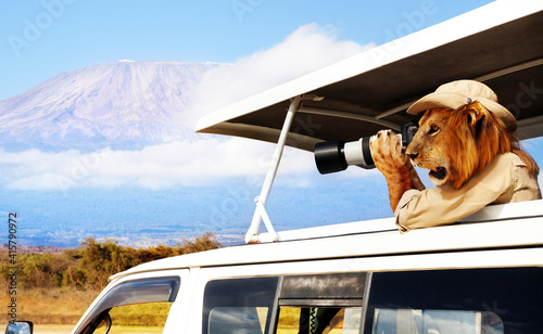 Photo Concept of a tourist as a lion taking photos of Kenyan Kilimanjaro mountain from