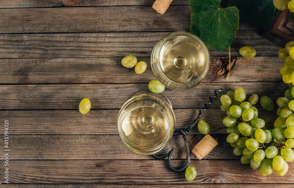 Fototapeta Two glasses of white wine and grape on vintage wooden table