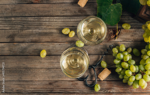 Two glasses of white wine and grape on vintage wooden table © juliamikhaylova
