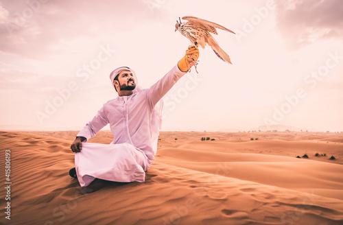 Arabic man with traditional emirates clothes walking in the desert with his falc Tapéta, Fotótapéta