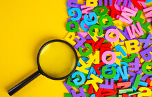 Magnifying Glass With Colorful Alphabet On Yellow Background, Copy Space.Education Concept.