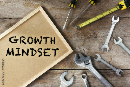 Obraz na plátně Growth mindset word on frame with tools supplies on wooden background