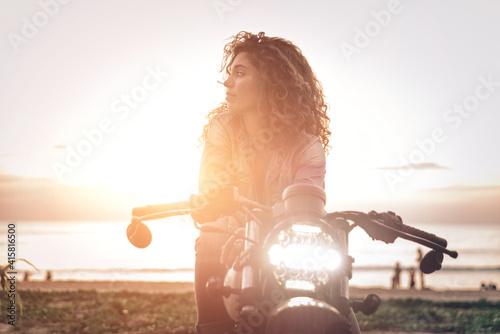 Fotografie, Obraz Beautiful girl having fun driving her custom cafe racer motorcycle, enjoying the