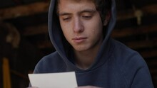 A Young Teen Boy Sits In A Garage Wearing A Hoodie. The Teenager Looks At A Photograph And Smiles With A Tear Running Down His Cheek.