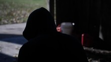 A Silhouette Shot Of A Young Teen Boy Wearing A Hoodie, Sitting In A Garage Alone, Brooding And Looking Sad.
