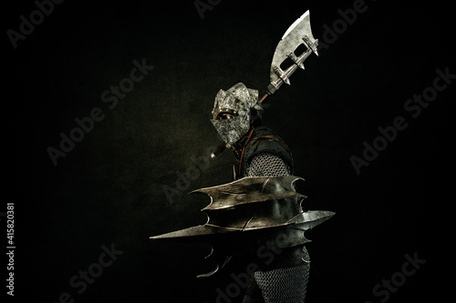 Photo Medieval fighter in armor, in profile, carrying a shield and an ax on his should