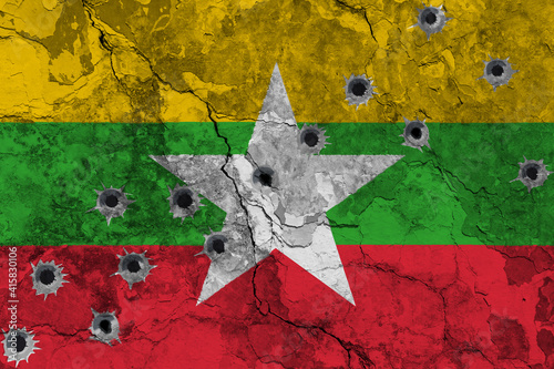 Billede på lærred Concept of the violent Conflict in Myanmar (Burma) with a painted flag on a cracked wall with wholes of bullets