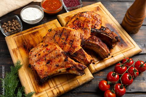 Fototapeta Grilled pork chops and vegetables on rustic background obraz