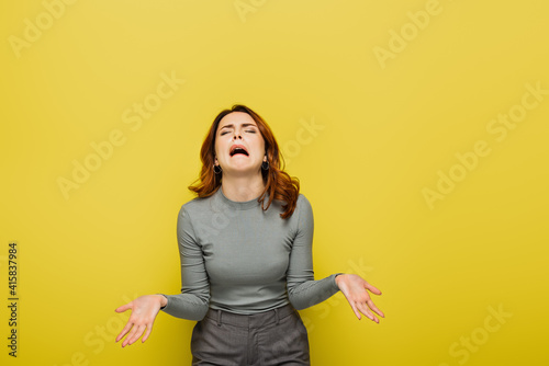Photo frustrated woman whining and gesturing isolated on yellow