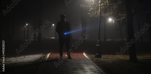 detective with a flashlight in the forest at night in the fog - fototapety na wymiar