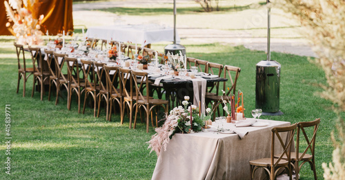 Fotografija Chairs and table for newlyweds decorated with candles, served with cutlery, croc