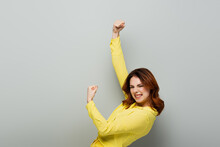 Excited Woman Looking At Camera And Showing Triumph Gesture On Grey