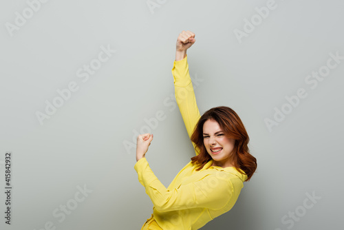 excited woman looking at camera and showing triumph gesture on grey Fototapeta