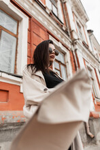 Gorgeous Young Woman Hipster In Vintage Sunglasses In Black Stylish Casual Wear In Spring Fashion Trench Coat Whirls Outdoors Near Old Building On Street. Trendy Urban Girl Fashion Model In City.