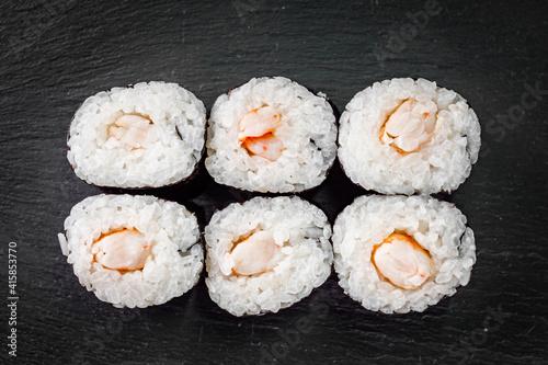 Fototapeta appetizing sushi shrimp maki roll on a black stone plate obraz