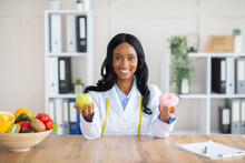 Pretty Black Dietary Doctor Holding Donut And Apple At Her Office, Offering Choice Between Fresh And Unhealthy Foods