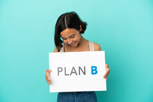Young Mixed Race Woman Isolated On Blue Background Holding A Placard With The Message PLAN B