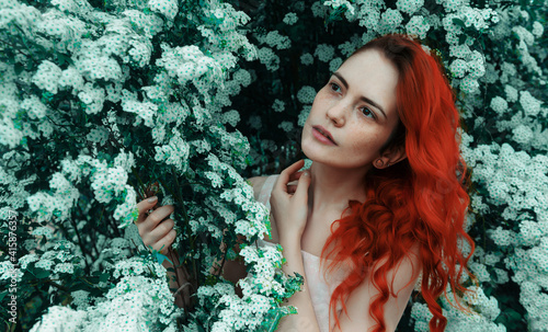 Obraz young  woman with red hair and freckles on the background of a bush with white flowers, beauty, spring - fototapety do salonu