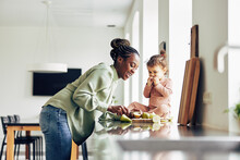 Smiling Mom And Her Cute Little Daughter Eating A Healthy Snack