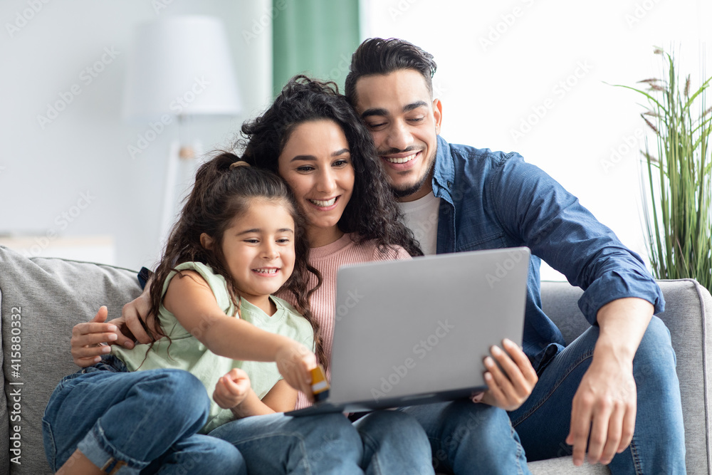 Fototapeta Online Shopping. Happy Arabic Family Using Laptop And Credit Card At Home