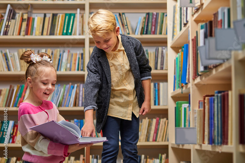 Obraz na plátně school kids preparing for lesson in school library, reading textbooks together a