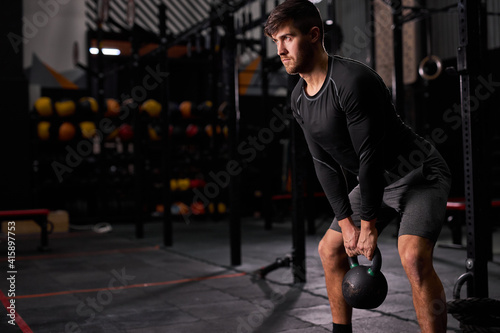 Fényképezés man with big muscles holding heavy kettlebell for cross fit swing training hard core workout in the gym, alone, wearing sportive clothes